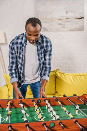 smiling young african american man playing table football at home 版權商用圖片