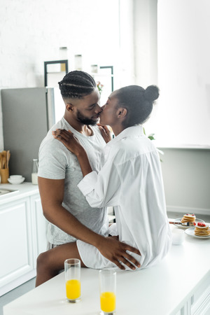 passionate african american couple kissing on kitchen counter at kitchen