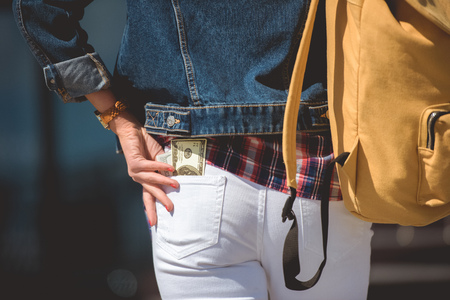 cropped image of stylish female tourist with backpack and dollar banknote in pocket of jeans Stock Photo