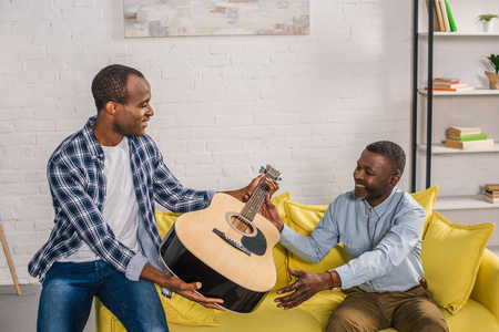 african american father and adult son holding acoustic guitar at home Stock Photo