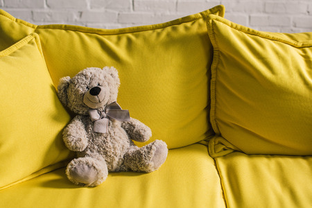 teddy bear on yellow couch in cozy room