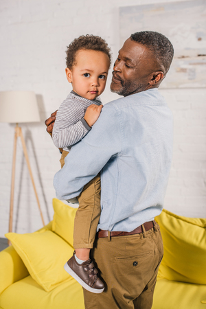 happy african american grandfather carrying adorable little grandchild at home 版權商用圖片 - 106690319