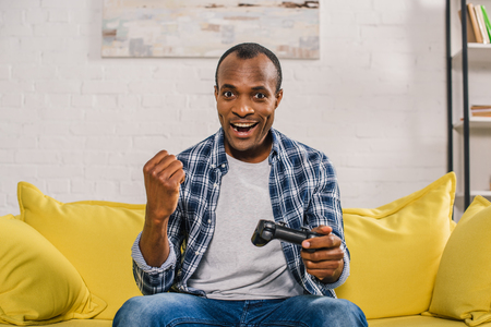 cheerful african american man smiling at camera while playing with joystick at home