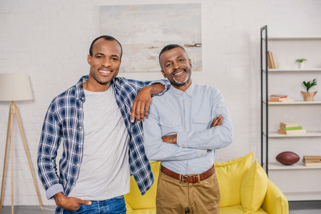happy african american father and adult son standing together and smiling at camera at home Stok Fotoğraf