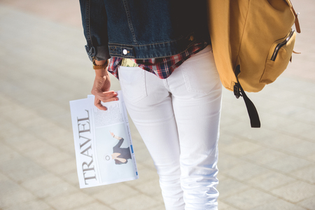 cropped image of stylish female tourist with backpack and travel newspaper Stock Photo