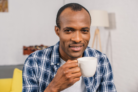young african american man holding coffee cup and smiling at camera 版權商用圖片 - 106690357