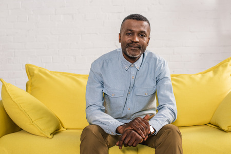 senior african american man sitting on yellow couch and smiling at camera
