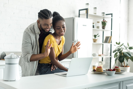 african american couple waving hands during video call at kitchen