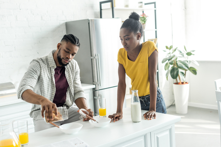 african american boyfriend pouring out cornflakes into plate at kitchen
