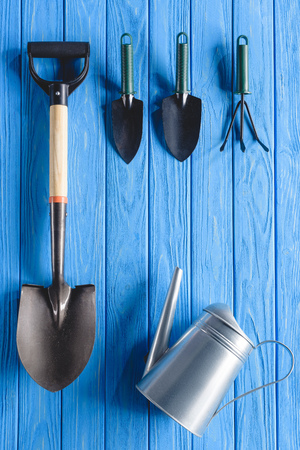 top view of watering can and gardening equipment on blue wooden planks