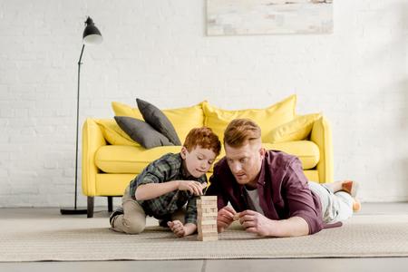 konzentrierter rothaariger Vater und Sohn liegen auf Teppich und spielen zu Hause mit Holzklötzen