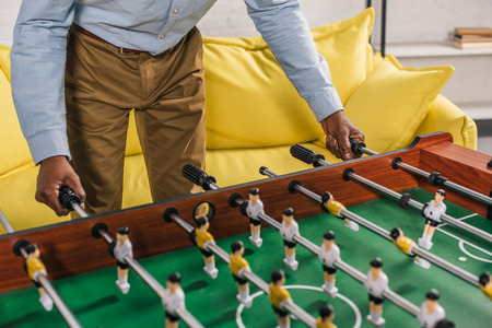 cropped shot of senior african american man playing table football at home