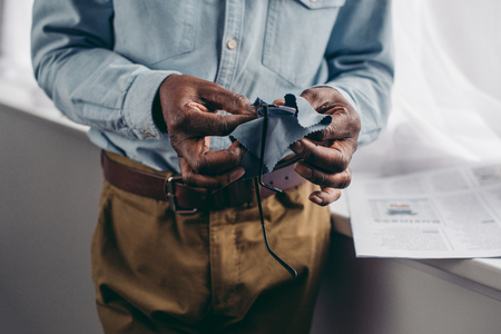 cropped shot of senior african american man cleaning eyeglasses with cloth