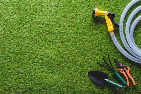 top view of hosepipe, hand rake, spade and secateurs on grass