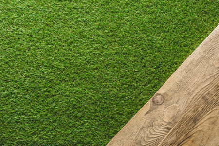 top view of green lawn and wooden plank background Фото со стока