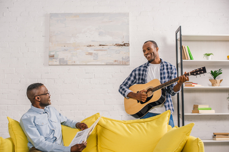 happy senior man with newspaper and smiling adult son with guitar looking at each other at home