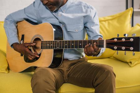 cropped shot of senior african american man playing acoustic guitar at home 版權商用圖片 - 106690536