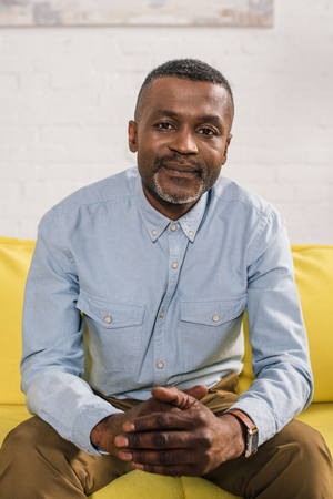 senior african american man sitting on couch and looking at camera