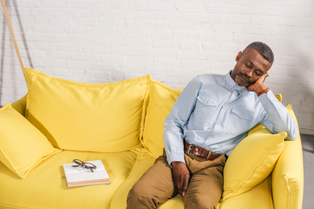 senior african american man sleeping on couch, book and eyeglasses on sofa Stock Photo