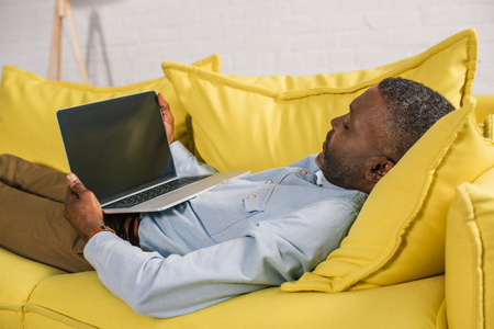 african american man using laptop with blank screen while lying on sofa