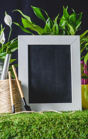 closeup shot of empty blackboard and gardening tools on grass