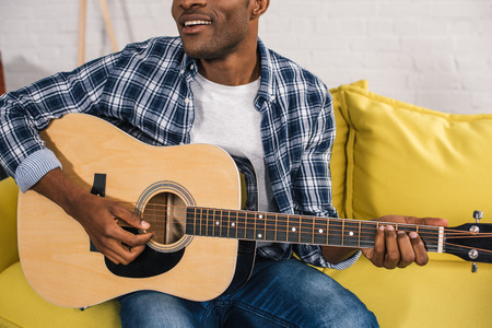 cropped shot of smiling african american man playing acoustic guitar at home Stock Photo