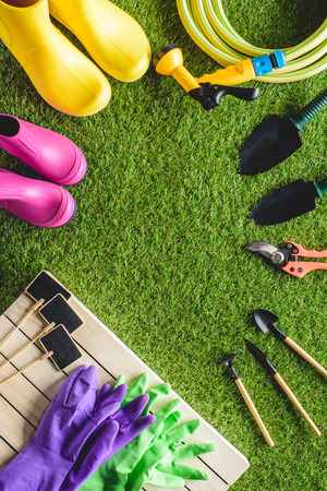 top view of empty blackboards, rubber boots, protective gloves and gardening equipment on grass Reklamní fotografie
