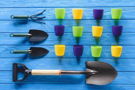 top view of colorful flower pots in row and gardening equipment on blue wooden planks