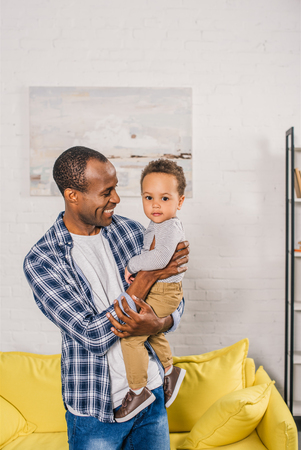 happy young father carrying adorable little son at home Stock Photo