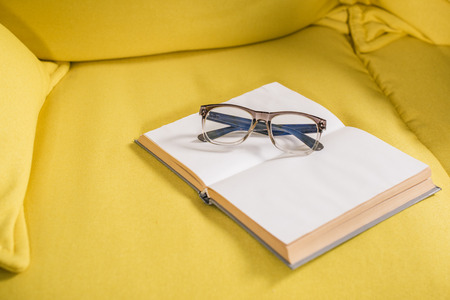 close-up view of eyeglasses and book with blank pages on yellow couch Stock Photo