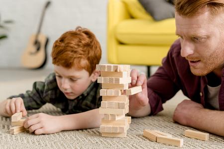 bijgesneden schot van geconcentreerde vader en zoon bouwen torens van houten blokken thuis Stockfoto