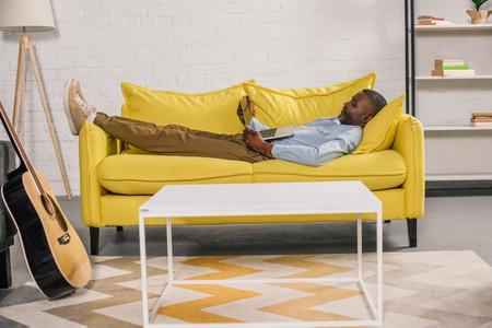 senior african american man lying on sofa and using laptop Stock Photo