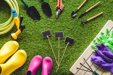 top view of empty blackboards surrounded by rubber boots, gardening equipment and protective gloves on grass