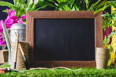 closeup shot of empty blackboard and gardening equipment on lawn
