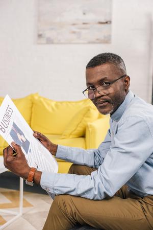 senior african american man in eyeglasses holding newspaper and looking at camera Reklamní fotografie