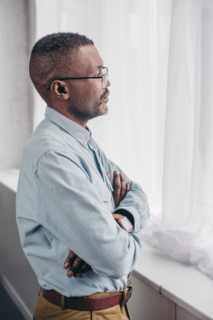 side view of senior african american man in eyeglasses standing with crossed arms and looking at window