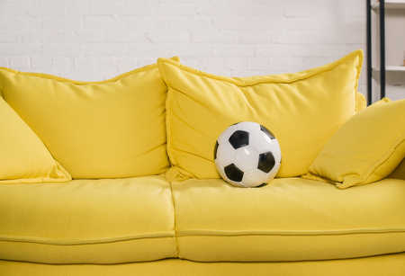 soccer ball on yellow couch in cozy room