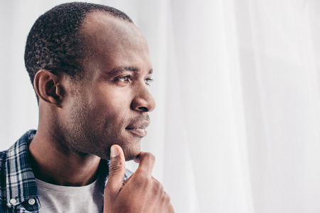close-up portrait of pensive african american man with hand on chin looking away 版權商用圖片 - 106733800