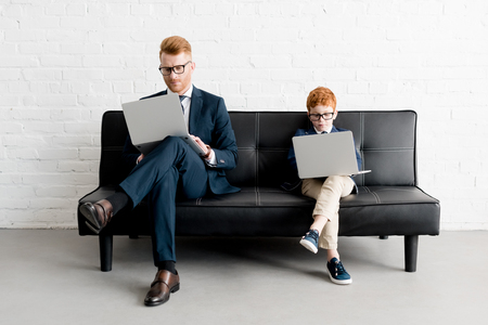serious father and little son businessmen wearing eyeglasses and using laptops 写真素材