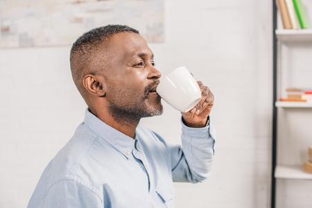 side view of senior african american man drinking coffee at home 版權商用圖片