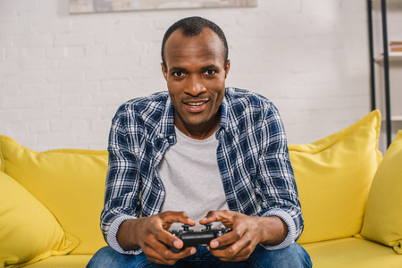 young african american man playing with joystick and smiling at camera 版權商用圖片 - 106734160