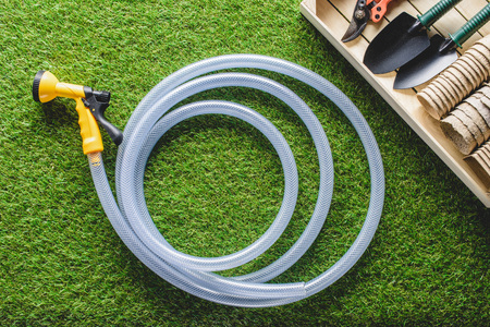 top view of hosepipe and gardening equipment on planks