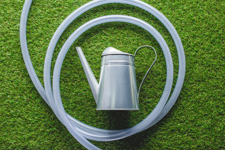 top view of watering can surrounded by hose on grass Stock Photo