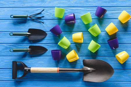 top view of gardening equipment and colorful flower pots on blue wooden planks