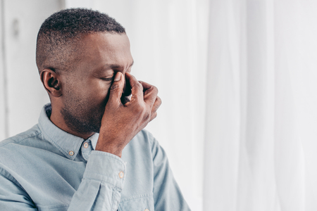 tired senior african american man rubbing bridge of nose