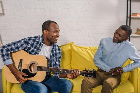 smiling senior man looking at adult son playing guitar at home Stock Photo