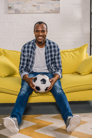 cheerful african american man holding soccer ball and smiling at camera while sitting on couch Stok Fotoğraf