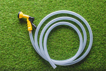 top view of hosepipe on green grass, minimalistic conception