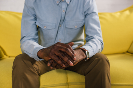 cropped shot of senior african american man sitting on yellow couch 版權商用圖片 - 106734249