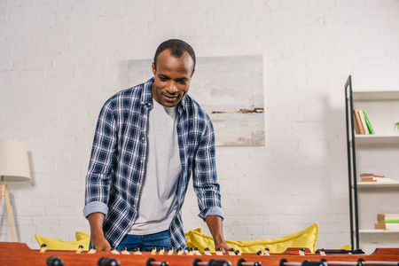 smiling young african american man playing table football at home Reklamní fotografie
